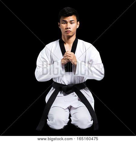 Portrait Of A Handsome Asian Man With Taekwondo Black Belt . Isolated On Black Background