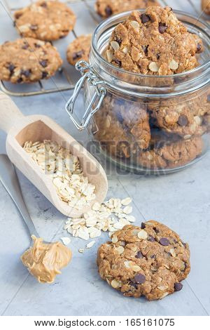 Flourless gluten free peanut butter oatmeal and chocolate chips cookies in glass jar and on table vertical
