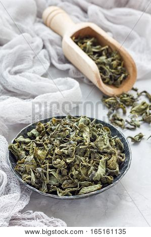 Dry green tea leaves on metal plate and on background vertical