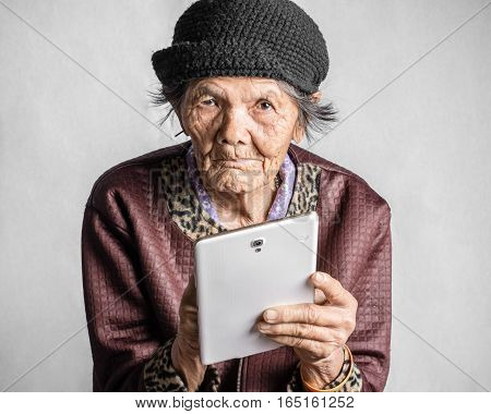 Portrait Of A Senior Woman With Tablet In Vintage Costume. Isolated On Grey Background