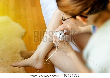 Woman using painless hair removal device with pulsating laser light on her calf leg for shiny and smooth fashion skin