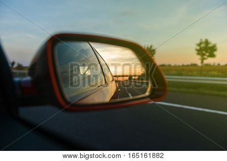 Vintage look of road and trees reflected in rear-view mirror while driving through agricultural field