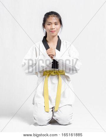 Portrait Of A Beutiful Asian Girl With Taekwondo Yellow Belt. Isolated On Grey Background