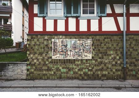 BADEN-BADEN GERMANY - NOV 20 2014: Vintage cobbler shoemaker manufacture process sign on hte facade of an old building in Baden-Baden Germany