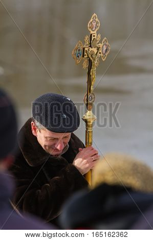 Rovzhi Ukraine - January 19 2014 Christian holiday Baptism in the Orthodox calendar. The man bowed his head in prayer holding orthodox cross with the crucifixion of Jesus.