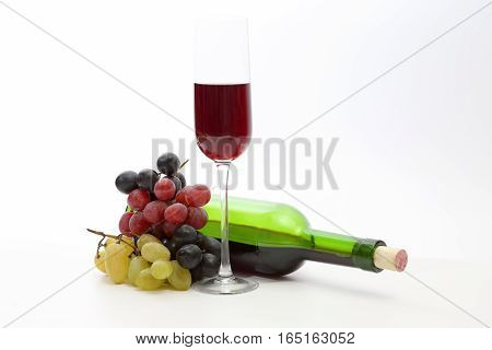 glass of red wine and bottle with grapes on a white background