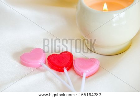 Red and pink shaped hearts resting on silk with a lit candle in the background. Valentine's day, wedding, anniversary, romantic symbol of love.  Relaxing spa setting.