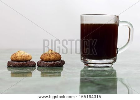 cup of hot black coffee with biscuits