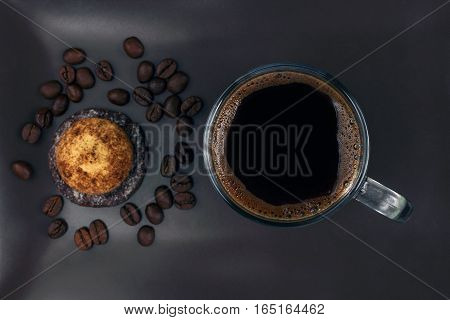 cup of black coffee with biscuits on a dark plate