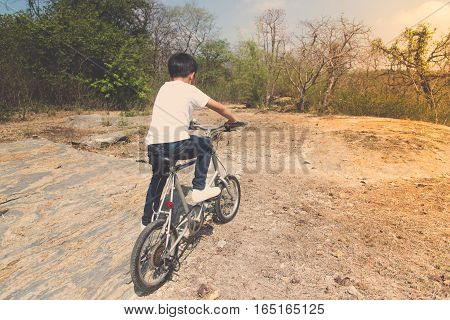 Little Boy Ride Bicycle On The Rock Road.