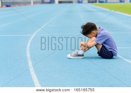 Young Asian Boy Sit On Blue Track In The Stadium