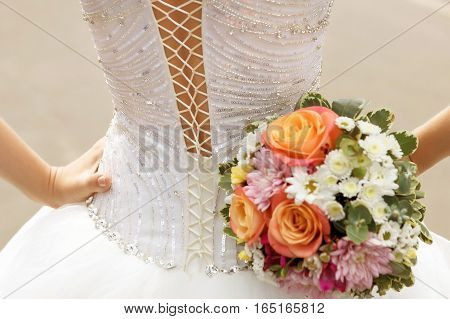 white lace corset wedding dress of the bride and the bridal bouquet
