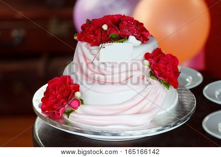 Pink and white festive cake decorated with flowers made of gum paste on the background of balloons. Soft focus selective focus
