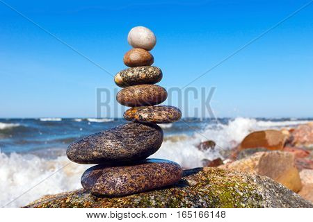 pyramid of wet stones on a background of the storm sea. unstable structure