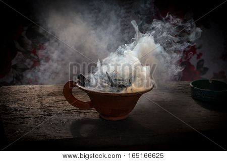 Steaming clay cup with spices on wooden table. Still-life on a black background. Pokhara Nepal. Close up