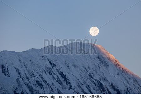 Beautiful landscape in Himalayas Annapurna region Nepal. Full moon during a sunrise on the background of snow-capped mountains