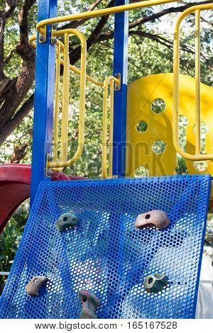 Artificial rock climbing wall at playground stock photo