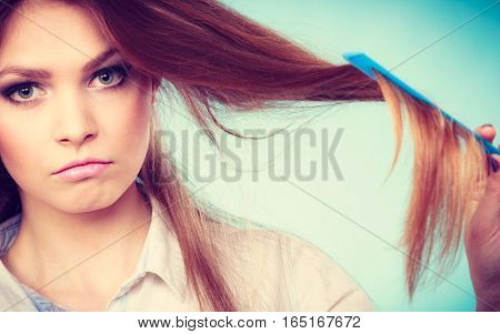 Healthy look concept. Girl combing brushing her hair by using plastic comb. Young woman taking care of everyday hygiene and natural beauty.