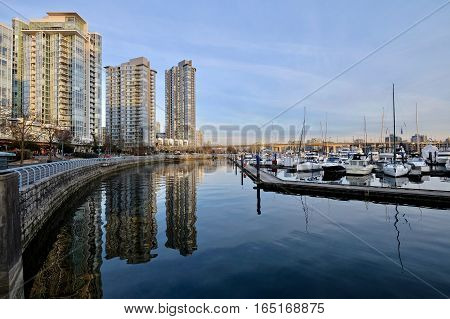Seawall, buildings, boats and their reflections in calm water. Yaletown. Cambie Bridge. False Creek. Vancouver downtown. British Columbia. Canada.