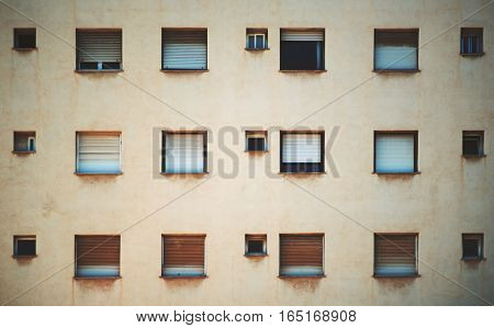 Beige facade of residential building in Barcelona with regular pattern of windows of different size streaks of rust under the sills
