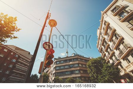Wide angle view of red traffic light and electric pole at the crossroad surrounded by beige and red residential houses bright sunny summer day in Barcelona Spain