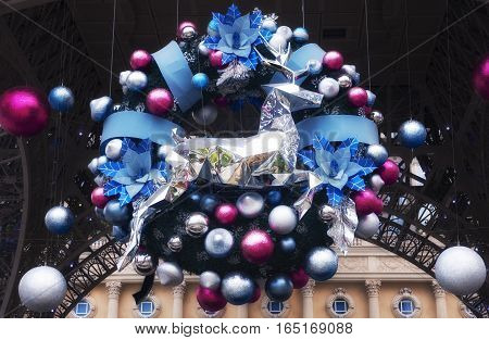 A christmas wreath with a silver reindeer leaping over ornaments on a holiday display in Macao china.