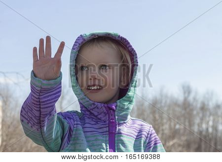 horizontal close up image of a two year old little caucasian girl waving goodbye with her hand