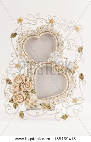 vertical image of a picture frame of two hearts mid an intertwined wire of flowers and lace imitation and two white doves on white background with room for text great for greeting card idea.