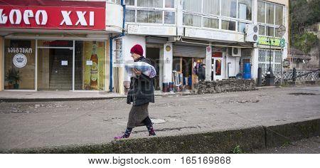 KUTAISI GEORGIA - FEBRUARY 23 2016: Woman carries goods walking on old street.