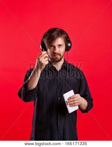 Man listening to your favorite music on headphones. He is holding a phone. Hipster in a black shirt on a red background.