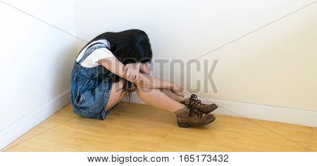 Woman sitting strain ,unhappy In the corner on the bow the knee In the corner of the room, even when the light shines,White and black,blur