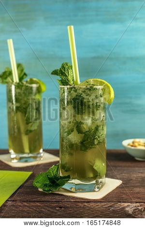 A photo of mojito cocktails with mint leaves, wedges of lime, drinking straws and a snack, on a vibrant teal wooden background with copy space. Selective focus