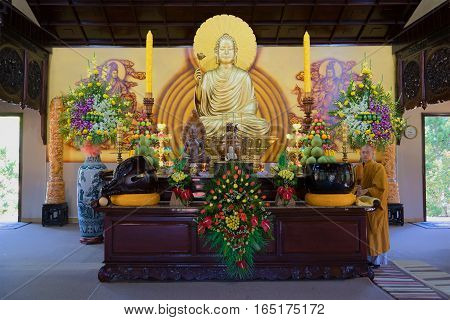 DA LAT, VIETNAM - DECEMBER 28, 2015: The Buddhist monk at an altar with the sitting Buddha in one of pagodas of Thien Vien Truc Lam Monastery