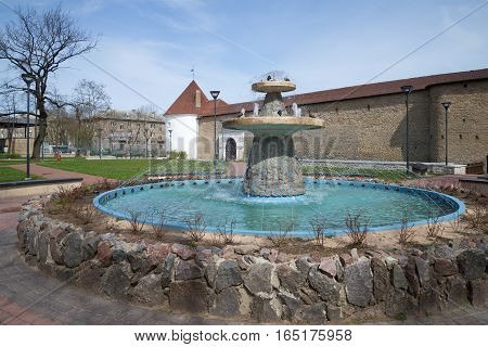 The city fountain at walls of the Herman castle in the sunny spring afternoon. Narva, Estonia