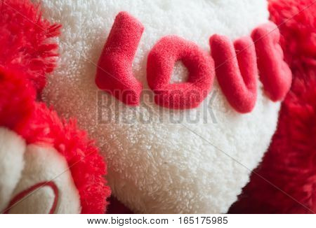 Soft focused photo of Red love word on teddy bear for Valentines Day with white heart on wooden floor with sunlight