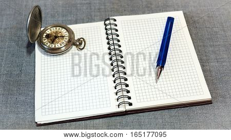 watch and Notepad with pen on a gray background