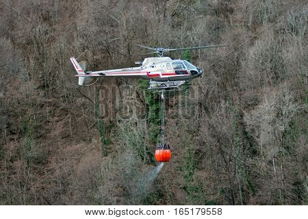 Helicopter transporting a bucket full of water suspended below the plane as it fights a mountain fire in the wilderness
