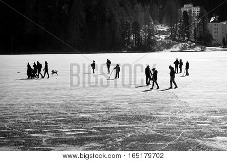 Silhouetted group of people and pets walking on a frozen lake in winter with urban buildings in the background
