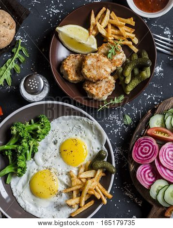 Lunch or snack table - fried eggs chicken balls potato chips vegetables sauces on a dark background. Rustic style top view. Flat lay