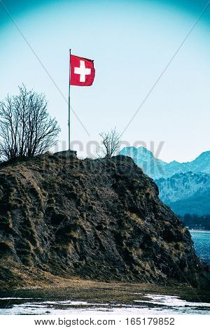 Swiss Flag Flying Above A Mountain