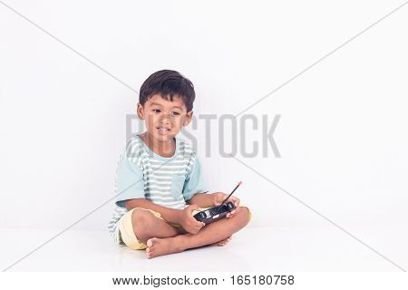 cute little asian boy play semi-automatic toy car on white background