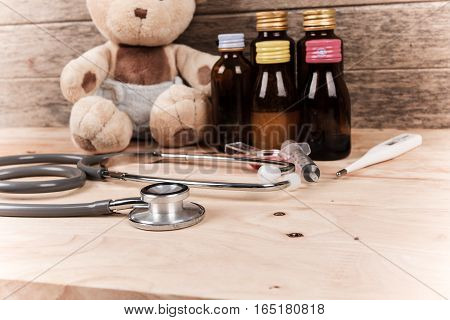 brown baby teddy bear with stethoscope and medicine