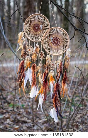 Brown and beige Dreamcatcher with boy and girl charms made of feathers leather beads and ropes hanging