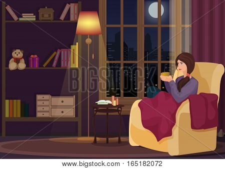 Young woman at home sitting in soft chear relaxing in her living room and drinking coffee or tea. Girl rests in night interior