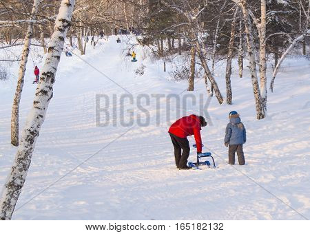 The father helps his son to correct the snowmobile, rolled down hill