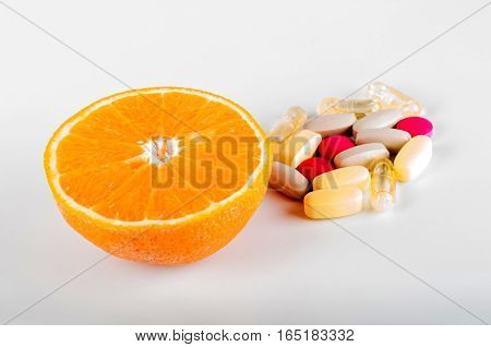 Fruits vs synthetic vitamins on white background