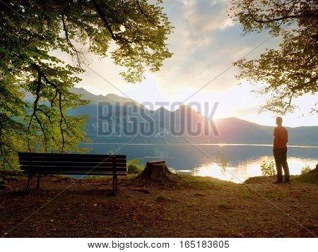 Man In Red Tshirt Walk At Lake Bank.  Empty Wooden Bench, Tree Stump