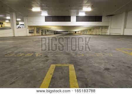 Empty Car Parking Garage at night with dirty floor.