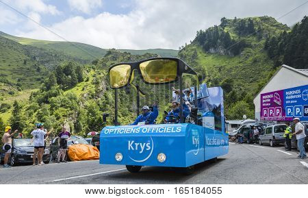 Col du Tourmalet France - July 242014: Krys caravan during the passing of the Publicity Caravan on the road to Col de Tourmalet in the stage 18 of Le Tour de France 2014.Before the appearance of the cyclists there is a caravan of advertising cars of the a