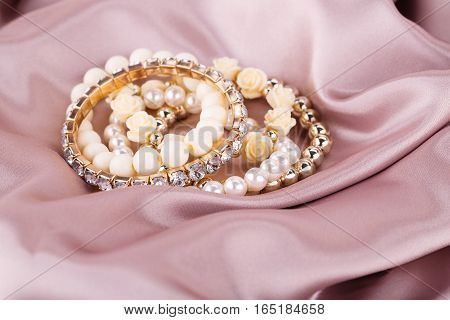 Stylish bracelets with pearls and stones on fabric background.